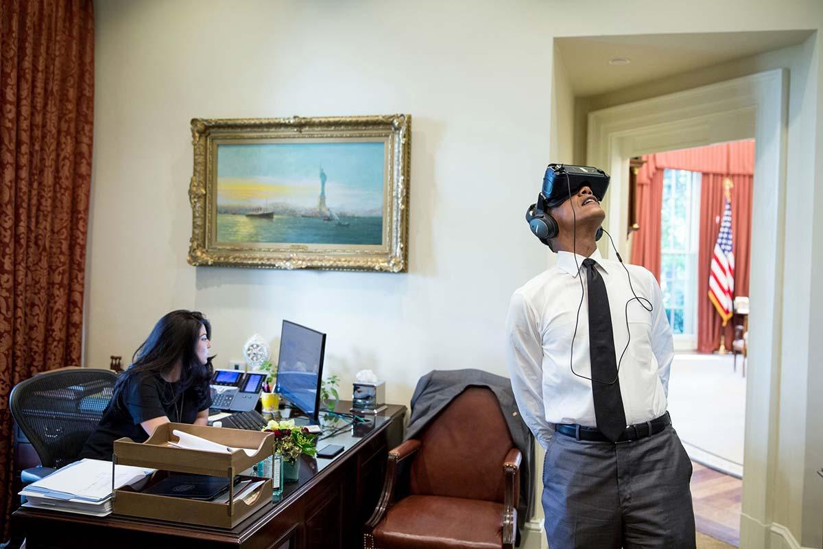 Il Presidente Barack Obama utilizza un visore di realtà virtuale all'esterno dello Studio Ovale, 24 agosto 2016. A sinistra, l'assistente personale Ferial Govashiri seduta alla propria scrivania. Official White House Photo by Pete Souza.